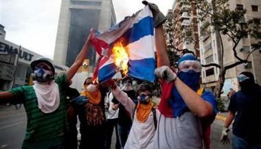 Miembros de la oposición venezolana queman una bandera cubana.